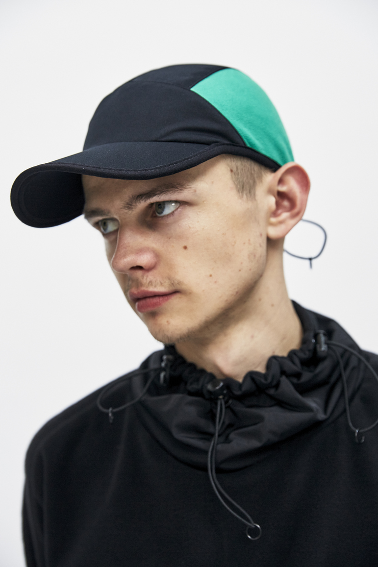 Fleece Panel Trek Cap from Cottweiler's A/W 17 collection. The style features a black body with blue and green fleece side panels and a rear toggle fastening for an adjustable fit.