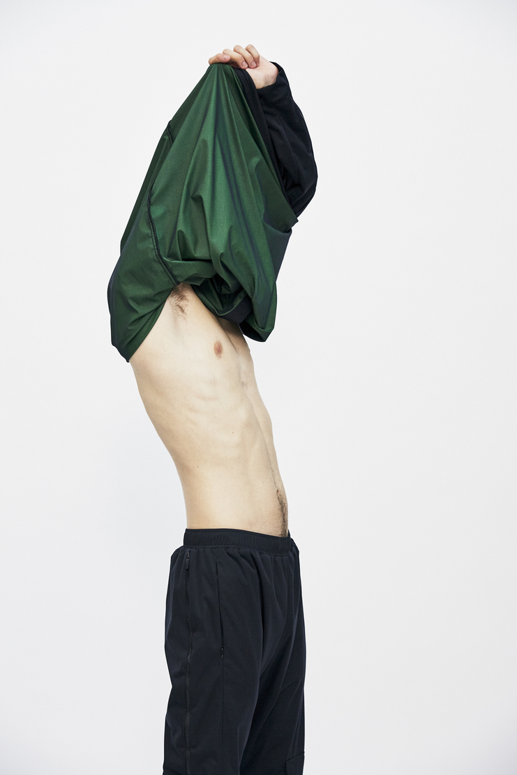 Black Utility Overshirt Smock from Cottweiler's A/W 17 collection. The overshirt features long sleeves with pockets, a front button fastening leading to a mandarin collar, a toggle hem and a forest green underside.