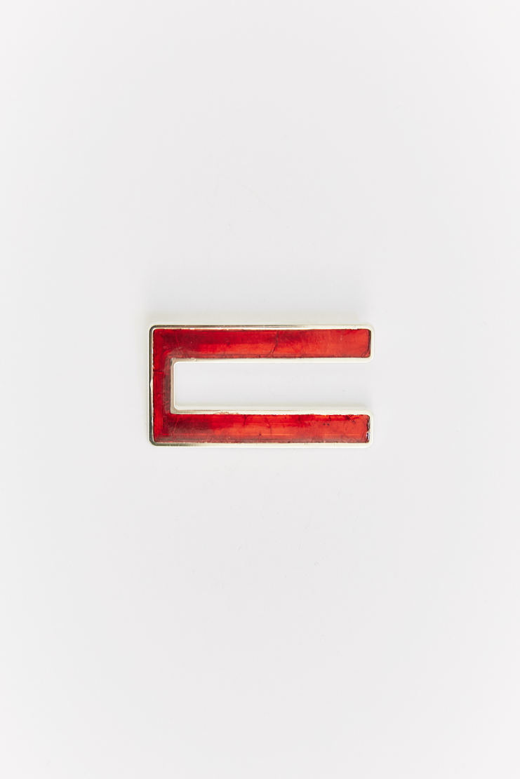 Pin from Raf Simons' A/W 17 collection, showcasing a silver-edged 'U' shape coloured in red. Made from 100% Silver.