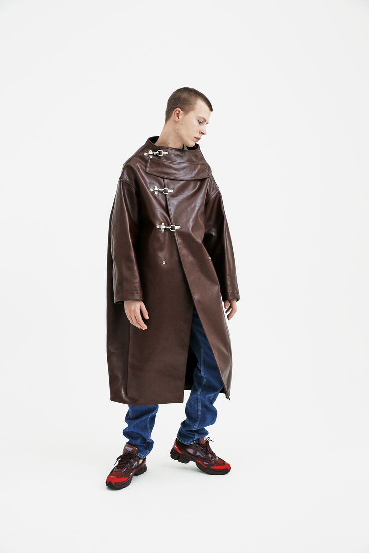 The dune coat from Raf Simons' iconic S/S 18 collection, treated to create a smooth leather-like material. The heavyweight long coat features long sleeves, a wide collarless neckline, and two side pockets. Finished with intrinsic metal buckle fastenings.